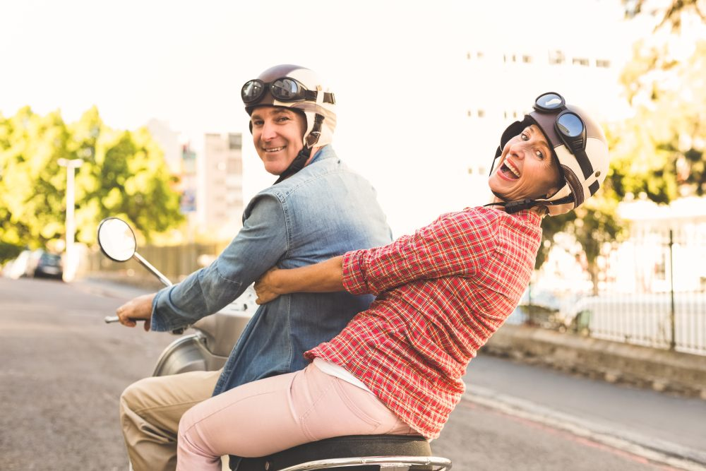 Senior couple riding in a two-seat electric scooter