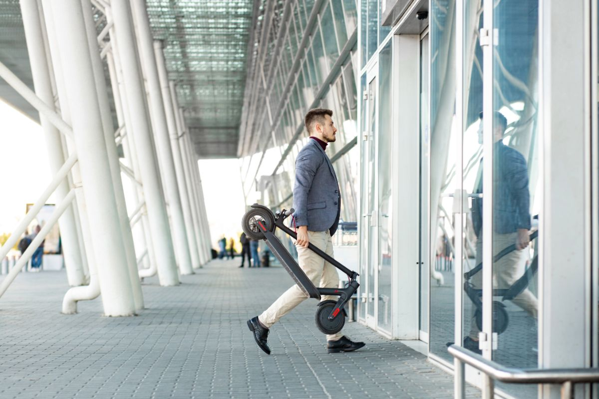 Man carrying folded electric scooter