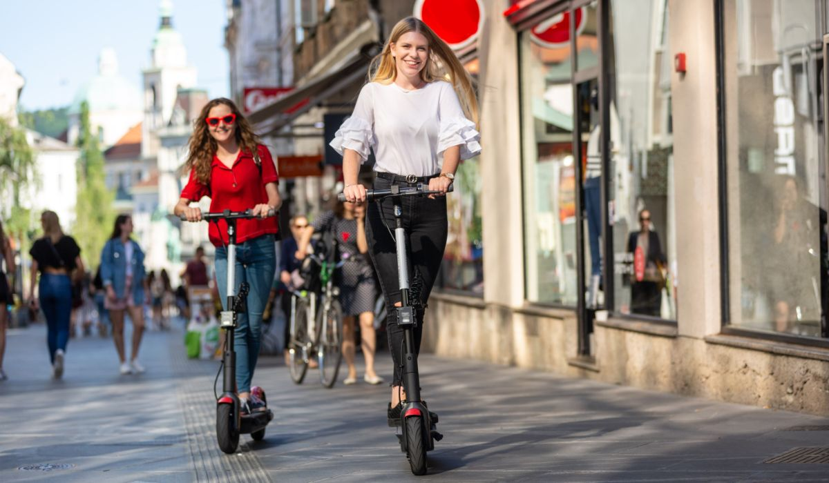 2 young woman riding electric scooter