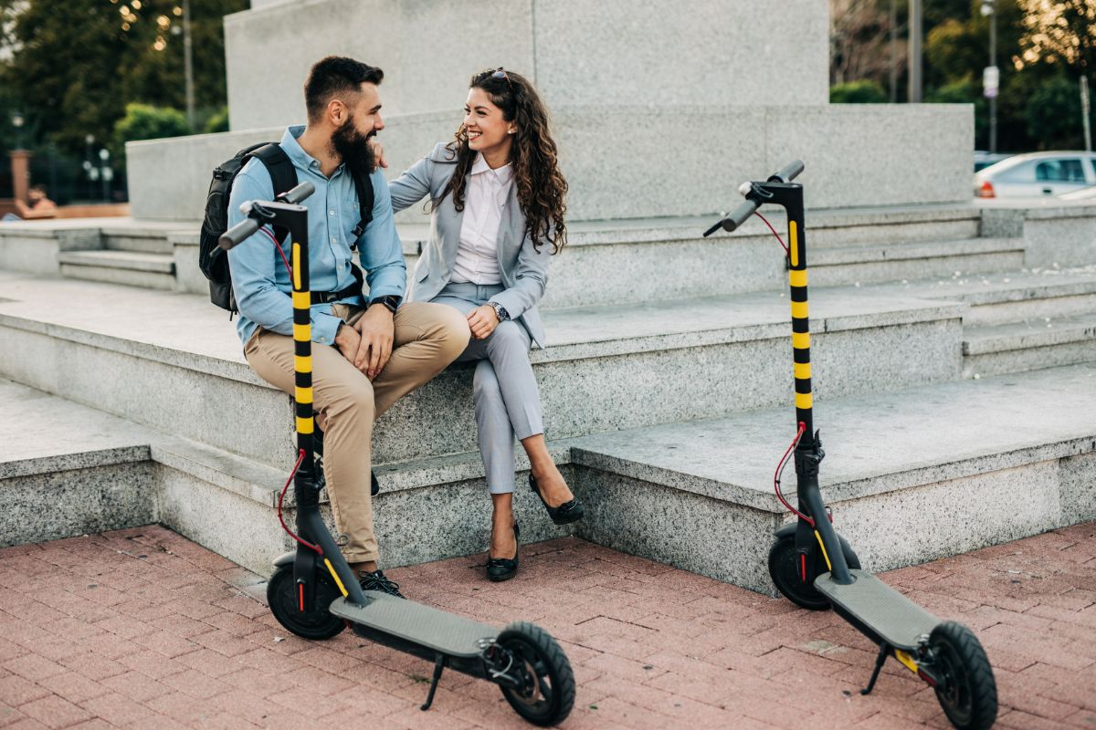 Couple resting with electric scooter