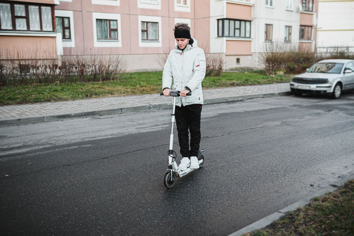 Man with white hoodie rinding electric scooter
