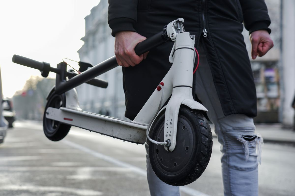 man holding foldable electric scooter