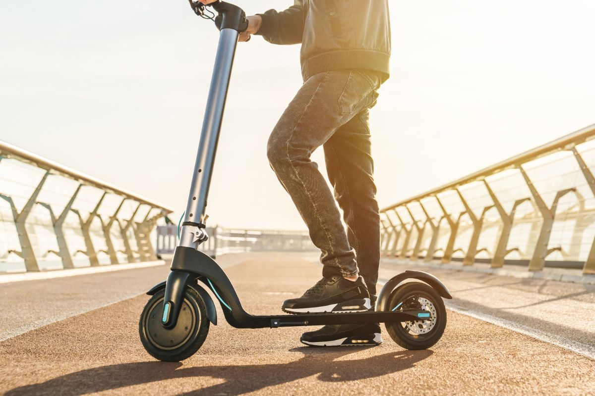 man standing on electric scooter