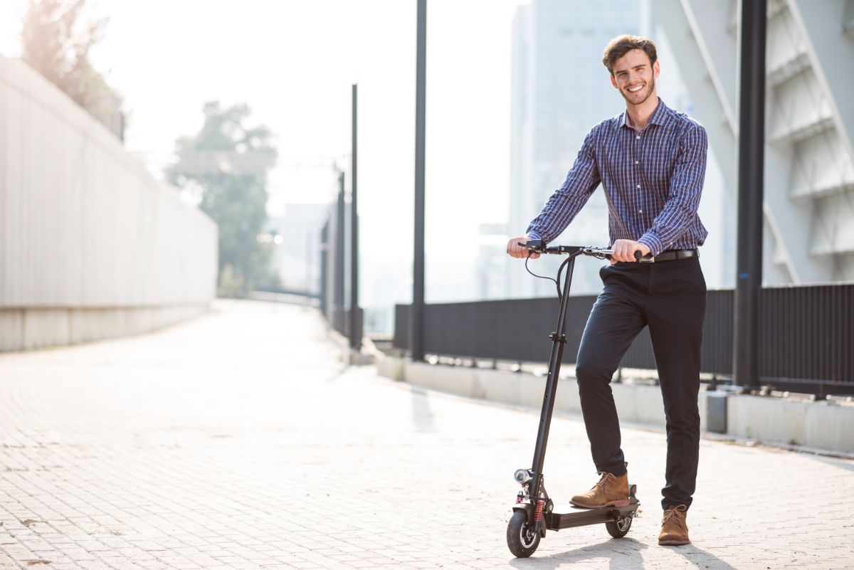 man standing next to his electric scooter