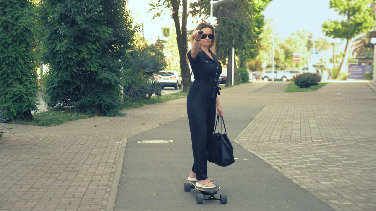 woman on business suit on electric skateboard