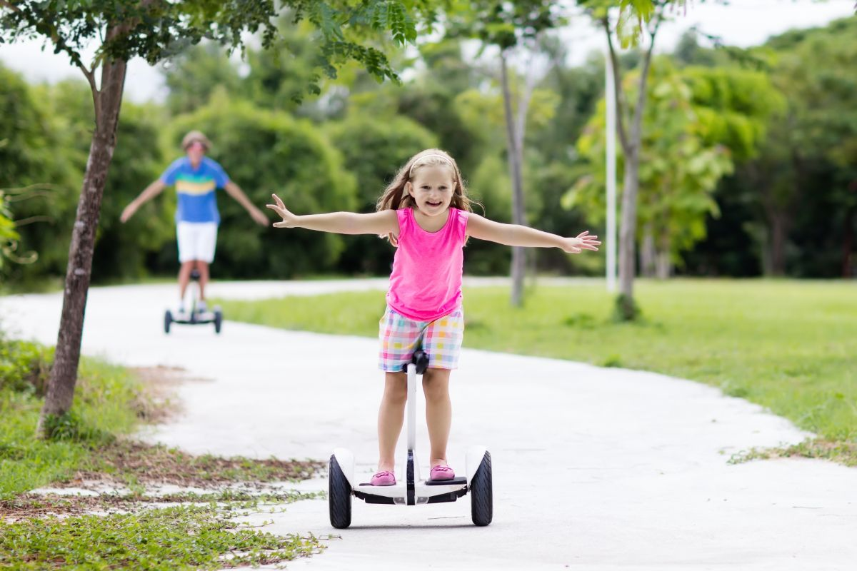 young girl happily riding electric scooter