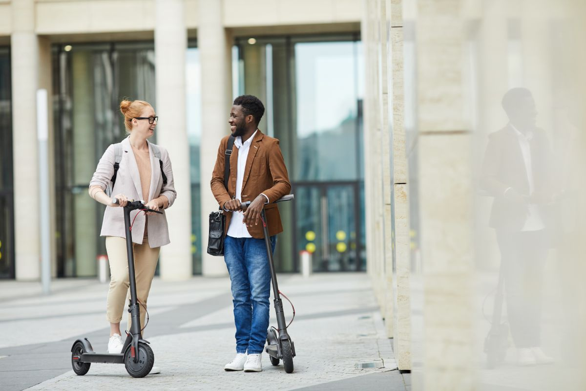 young man and woman riding with electric scooter