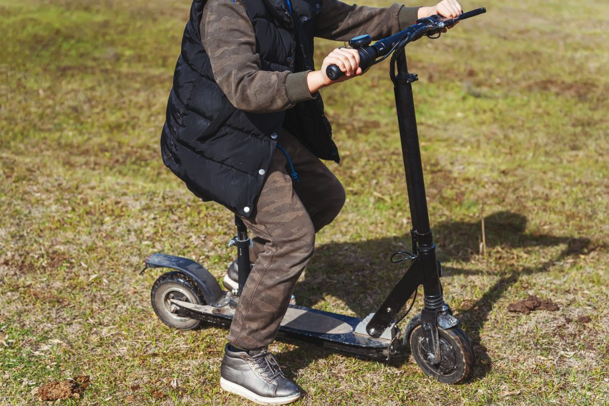 young man riding electric scooter with seat