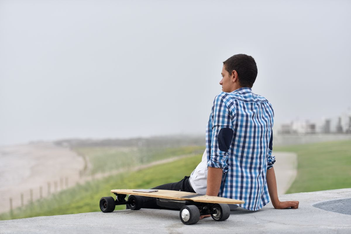 young man sits besides electric skateboard