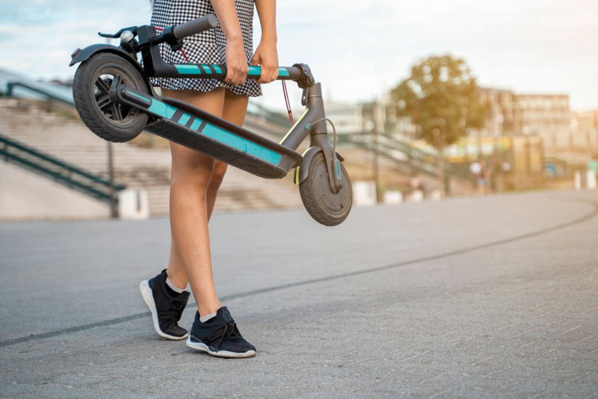 young woman holding her folded electric scooter